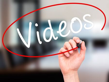 televisor: Man Hand writing Videos with black marker on visual screen. Isolated on office. Business, technology, internet concept. Stock Image Stock Photo