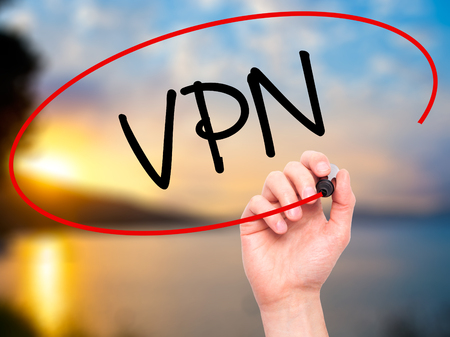 vpn: Man Hand writing VPN (Virtual Private Network) with black marker on visual screen. Isolated on background. Business, technology, internet concept. Stock Photo
