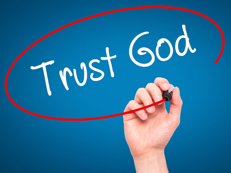 trust in god: Man Hand writing Trust God  with black marker on visual screen. Isolated on blue. Business, technology, internet concept. Stock Photo