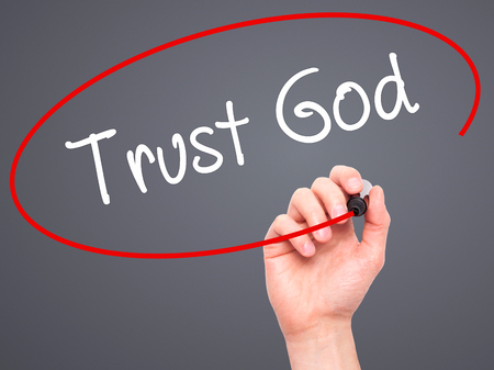 trust in god: Man Hand writing Trust God  with black marker on visual screen. Isolated on grey. Business, technology, internet concept. Stock Photo Stock Photo