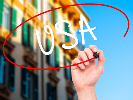 foreign country: Man Hand writing USA with black marker on visual screen. Isolated on city. Travel, technology, internet concept. Stock Photo