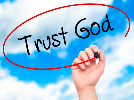 trust in god: Man Hand writing Trust God  with black marker on visual screen. Isolated on sky. Business, technology, internet concept. Stock Photo Stock Photo
