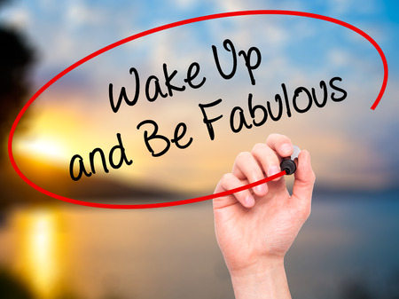 highway love: Man Hand writing Wake Up and Be Fabulous with black marker on visual screen. Isolated on background. Business, technology, internet concept. Stock Photo