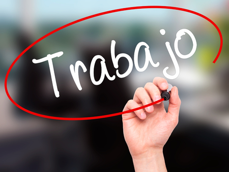 trabajo: Man Hand writing Trabajo  ( work in Spanish) with black marker on visual screen. Isolated on background. Business, technology, internet concept. Stock Photo