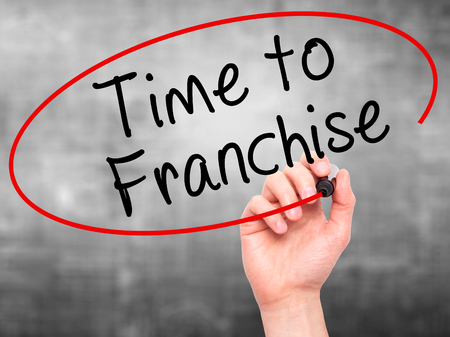 authorizing: Man Hand writing Time to Franchise with black marker on visual screen. Isolated on grey. Business, technology, internet concept. Stock Photo