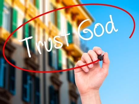 trust in god: Man Hand writing Trust God  with black marker on visual screen. Isolated on city. Business, technology, internet concept. Stock Photo