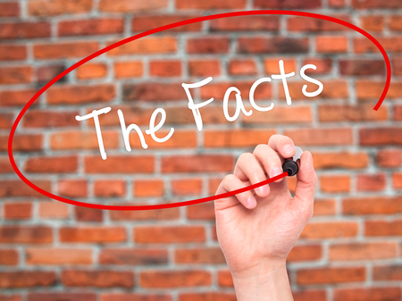 Man Hand writing The Facts  with black marker on visual screen. Isolated on bricks. Business, technology, internet concept. Stock Photo