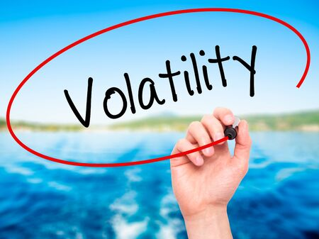 volatility: Man Hand writing Volatility with black marker on visual screen. Isolated on nature. Business, technology, internet concept. Stock Photo