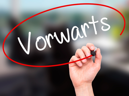 next horizon: Man Hand writing Vorw??¤rts  (Forward In German)  with black marker on visual screen. Isolated on office. Business, technology, internet concept. Stock Photo