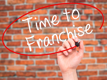 Man Hand writing Time to Franchise with black marker on visual screen. Isolated on bricks. Business, technology, internet concept. Stock Photo