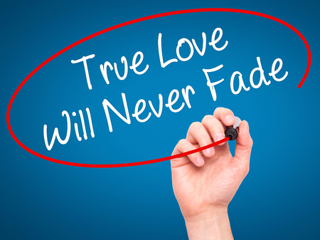 with true love: Man Hand writing True Love Will Never Fade with black marker on visual screen. Isolated on background. Business, technology, internet concept. Stock Photo Stock Photo