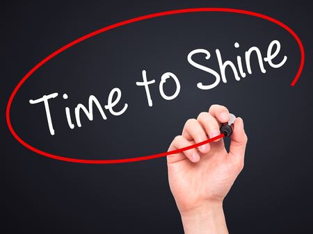 time to shine: Man Hand writing Time to Shine with black marker on visual screen. Isolated on black. Business, technology, internet concept. Stock Photo
