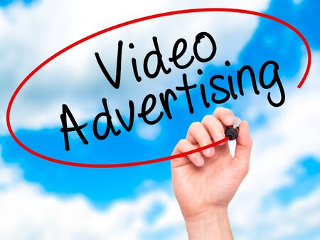 infomercial: Man Hand writing Video Advertising with black marker on visual screen. Isolated on sky. Business, technology, internet concept. Stock Photo Stock Photo