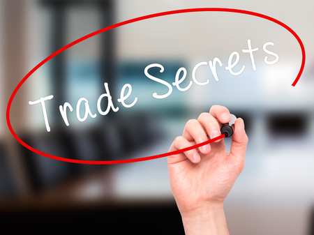 privileged: Man Hand writing Trade Secrets with black marker on visual screen. Isolated on office. Business, technology, internet concept. Stock Photo