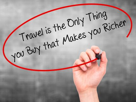 richer: Man Hand writing Travel is the Only Thing you Buy that Makes you Richer with black marker on visual screen. Isolated on grey. Business, technology, internet concept. Stock Photo Stock Photo