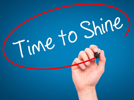 time to shine: Man Hand writing Time to Shine with black marker on visual screen. Isolated on blue. Business, technology, internet concept. Stock Photo