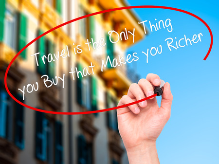 richer: Man Hand writing Travel is the Only Thing you Buy that Makes you Richer with black marker on visual screen. Isolated on city. Business, technology, internet concept. Stock Photo Stock Photo