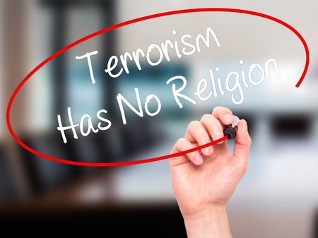 Man Hand writing Terrorism Has No Religion with black marker on visual screen. Isolated on office. Business, technology, internet concept. Stock Photo