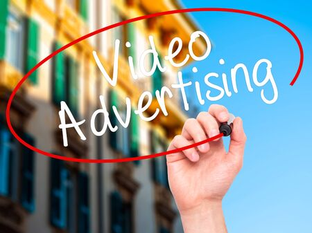 infomercial: Man Hand writing Video Advertising with black marker on visual screen. Isolated on city. Business, technology, internet concept. Stock Photo