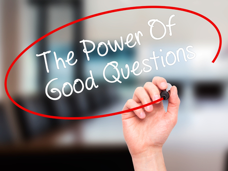 background information: Man Hand writing The Power Of Good Questions with black marker on visual screen. Isolated on office. Business, technology, internet concept. Stock Photo