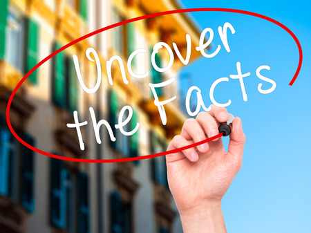 uncover: Man Hand writing Uncover the Facts with black marker on visual screen. Isolated on city. Business, technology, internet concept. Stock Image