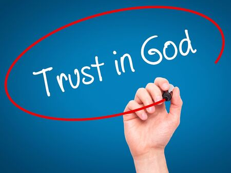 confessing: Man Hand writing Trust in God with black marker on visual screen. Isolated on blue. Business, technology, internet concept. Stock Photo Stock Photo