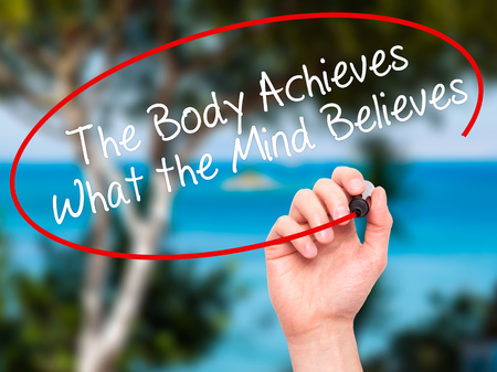 achieves: Man Hand writing The Body Achieves What the Mind Believes with black marker on visual screen. Isolated on nature. Business, technology, internet concept. Stock Photo