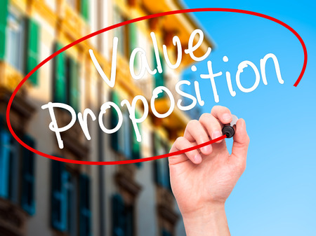 resonating: Man Hand writing Value Proposition with black marker on visual screen. Isolated on city. Business, technology, internet concept. Stock Photo Stock Photo