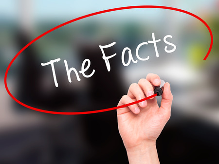 Man Hand writing The Facts  with black marker on visual screen. Isolated on office. Business, technology, internet concept. Stock Photo