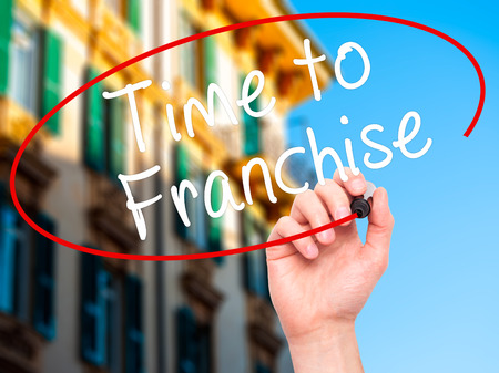 Man Hand writing Time to Franchise with black marker on visual screen. Isolated on city. Business, technology, internet concept. Stock Photo