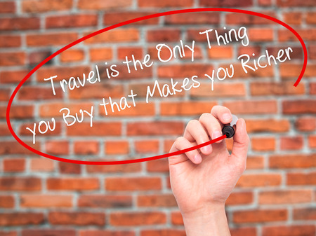 richer: Man Hand writing Travel is the Only Thing you Buy that Makes you Richer with black marker on visual screen. Isolated on bricks. Business, technology, internet concept. Stock Photo