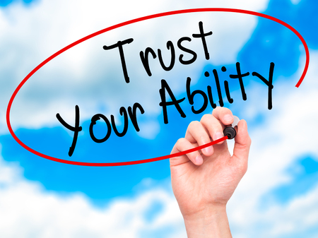 communication capability: Man Hand writing Trust Your Ability  with black marker on visual screen. Isolated on sky. Business, technology, internet concept. Stock Photo
