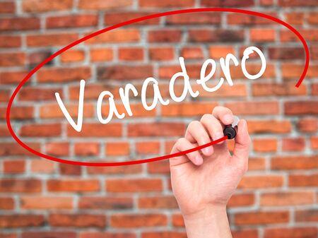 varadero: Man Hand writing Varadero with black marker on visual screen. Isolated on bricks. Business, technology, internet concept. Stock Photo Stock Photo