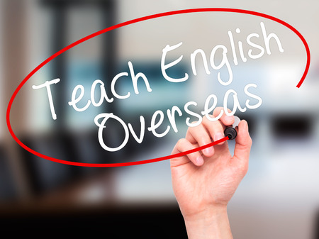 Man Hand writing Teach English Overseas with black marker on visual screen. Isolated on office. Business, technology, internet concept. Stock Photo