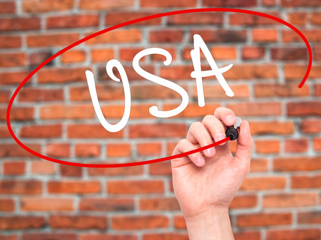 foreign country: Man Hand writing USA with black marker on visual screen. Isolated on bricks. Travel, technology, internet concept. Stock Photo