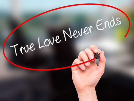 in loving memory: Man Hand writing True Love Never Ends with black marker on visual screen. Isolated on office. Business, technology, internet concept. Stock Photo