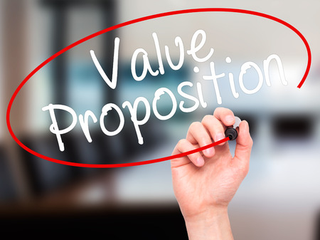 proposition: Man Hand writing Value Proposition with black marker on visual screen. Isolated on office. Business, technology, internet concept. Stock Photo