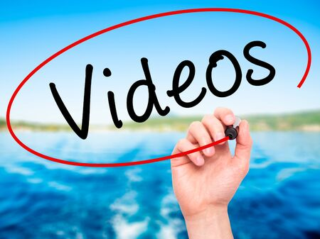infomercial: Man Hand writing Videos with black marker on visual screen. Isolated on nature. Business, technology, internet concept. Stock Image