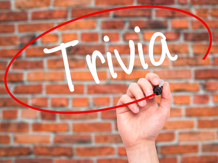 trivia: Man Hand writing Trivia with black marker on visual screen. Isolated on bricks. Business, technology, internet concept. Stock Photo