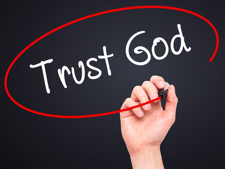 trust in god: Man Hand writing Trust God  with black marker on visual screen. Isolated on black. Business, technology, internet concept. Stock Photo