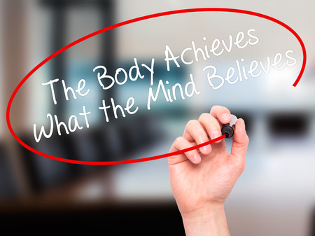 achieves: Man Hand writing The Body Achieves What the Mind Believes with black marker on visual screen. Isolated on office. Business, technology, internet concept. Stock Photo Stock Photo