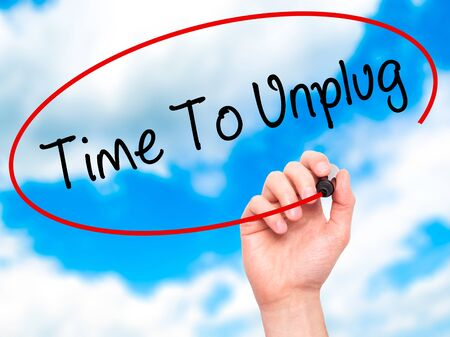 unplugging: Man Hand writing Time To Unplug with black marker on visual screen. Isolated on sky. Business, technology, internet concept. Stock Photo