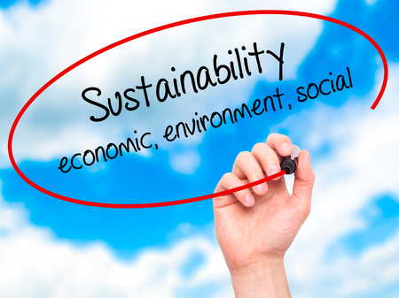 economic theory: Man Hand writing Sustainability  economic, environment, social with black marker on visual screen. Isolated on sky. Business, technology, internet concept. Stock Photo