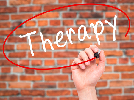 visual therapy: Man Hand writing Therapy with black marker on visual screen. Isolated on bricks. Business, technology, internet concept. Stock Photo Stock Photo