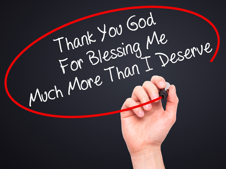 deserve: Man Hand writing Thank You God For Blessing Me Much More Than I Deserve with black marker on visual screen. Isolated on black. Business, technology, internet concept. Stock Photo