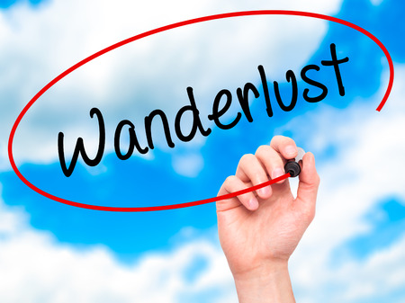 wanderlust: Man Hand writing Wanderlust with black marker on visual screen. Isolated on sky. Business, technology, internet concept. Stock Photo Stock Photo