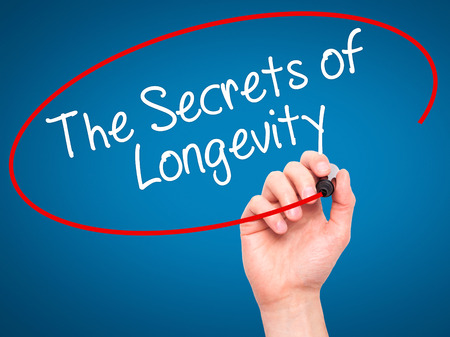 longevity: Man Hand writing The Secrets of Longevity with black marker on visual screen. Isolated on blue. Business, technology, internet concept. Stock Photo Stock Photo