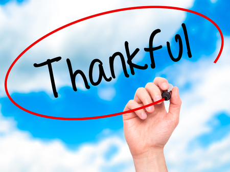 obliged: Man Hand writing Thankful  with black marker on visual screen. Isolated on background. Business, technology, internet concept. Stock Photo Stock Photo