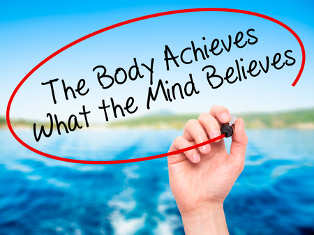 believes: Man Hand writing The Body Achieves What the Mind Believes with black marker on visual screen. Isolated on nature. Business, technology, internet concept. Stock Photo