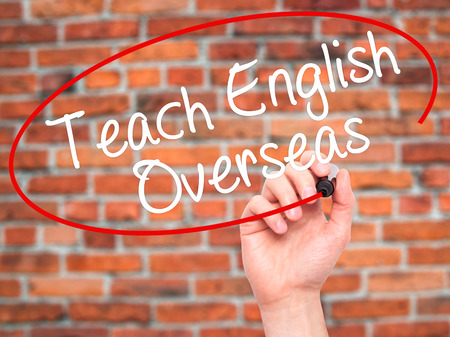 Man Hand writing Teach English Overseas with black marker on visual screen. Isolated on bricks. Business, technology, internet concept. Stock Photo